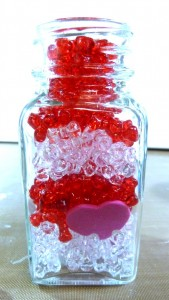 Salt shaker filled with beads and foam hearts.