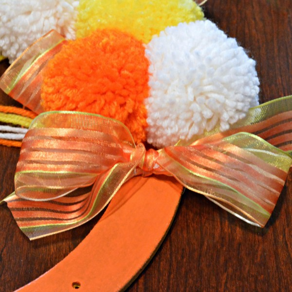 Bright, fluffy and Halloween-happy, Candy Corn Pompom Wreaths are candy-inspired holiday decor for doors or windows! At littlemisscelebration.com #crafts #halloween
