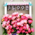 An old frame gets a fresh coat of white paint and is backed with floral mesh to hold masses of gorgeous silk, pink peonies for this Bursting with Blooms Door Wreath! at littlemisscelebration.com