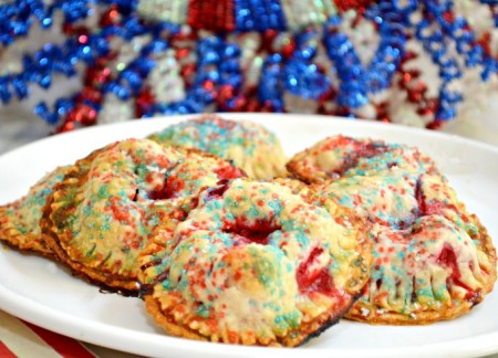 Refrigerated pie crust makes it easy to whip up a batch of grab-and-go Raspberry Hand Tarts! Jazz them up for the 4th with red, white & blue sanding sugar. Fun & easy! Recipe at littlemisscelebration.com